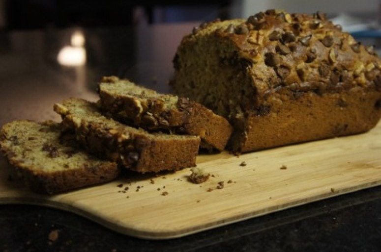 Lindsay's Banana Bread placed on a wooden cutting board. Ingredients include whole wheat flour, ground flax, eggs, banana, chocolate chips, walnuts.