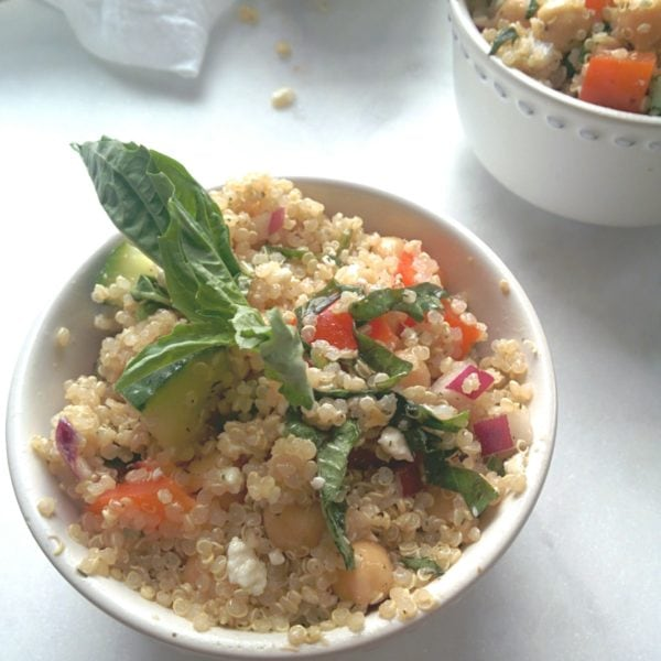 Mediterranean and Chickpea Quinoa Salad in a white round bowl. Ingredients include quinoa, chicken stock, red wine vinegar, grape tomatoes, onion, chickpeas, feta, basil, parsley.
