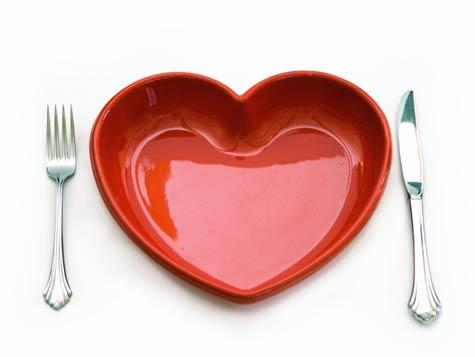 A heart shaped dish between a fork and a knife.