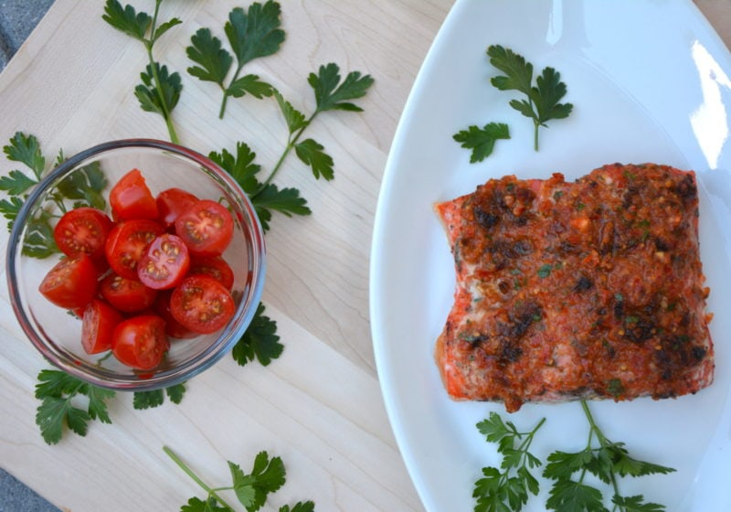 Baked Salmon with Sundried Tomato Aioli. Ingredients include salmon, sundried tomatoes, garlic, parsley, cherry tomatoes.