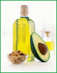 A bottle of oil placed on a counter with an avocado and a bowl of almonds.