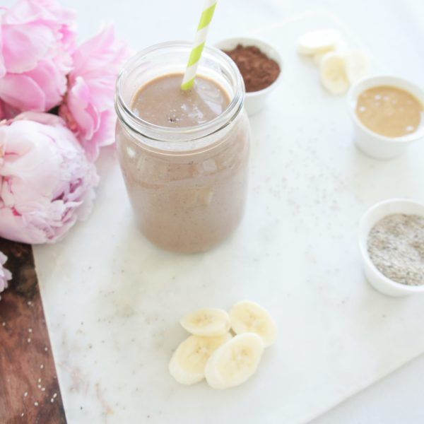 Creamy Chocolate Banana Chia Smoothie in a mason jar with a white and green striped straw on a marble food photography board. Ingredients include almond milk, chia seeds, cocoa, Greek yogurt, banana, nut butter, dates.