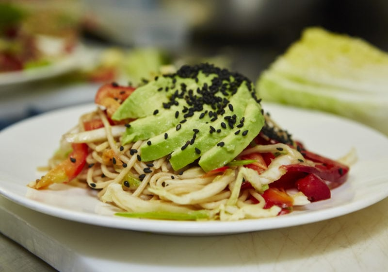 Chilled Noodle Salad with Ginger Wasabi Dressing. Ingredients include ancient grains spaghetti, snow peas, edamame, cucumber, cabbage, pepper, avocado, cilantro, sesame seeds.