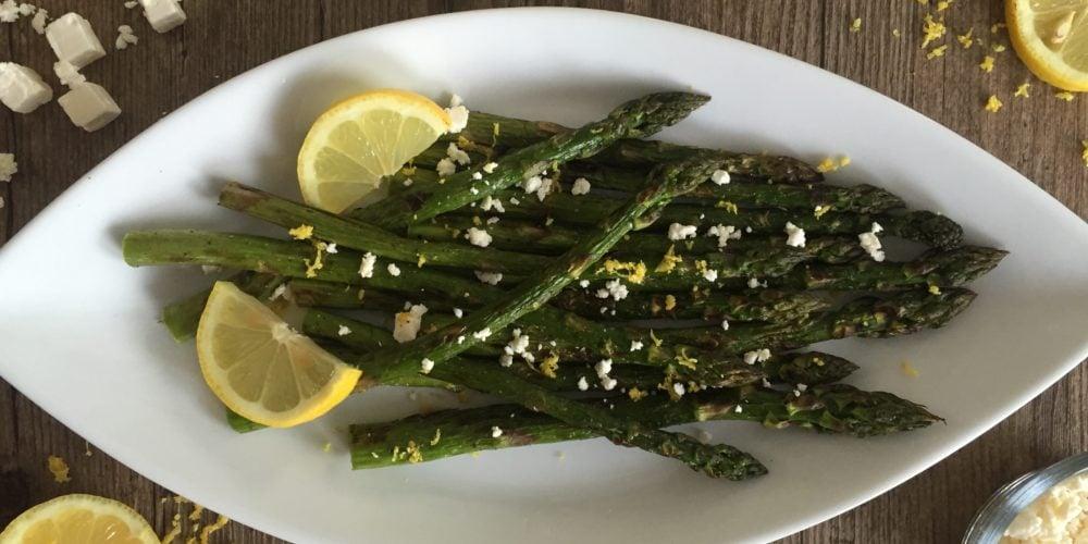 Grilled Lemon Asparagus and Feta Salad placed on a white serving dish. Ingredients include asparagus, lemon, feta.