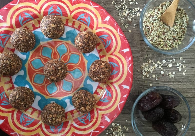Raw Chocolate Energy Bites on a colourful red, yellow, and blue plate. Ingredients include rolled oats, hemp hearts, chia seeds, dates, cocoa, natural peanut butter, vanilla.