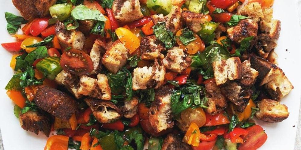 Panzanella Salad on a white serving plate. Ingredients include sourdough bread, garlic, balsamic vinegar, red wine vinegar, heirloom tomatoes, red pepper, yellow pepper, orange pepper, avocado, basil.