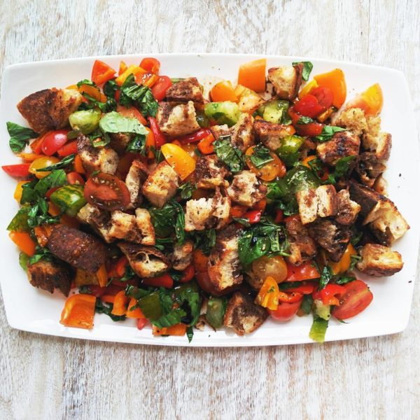 Panzanella Salad on a white serving plate. Ingredients include sourdough bread, garlic, balsamic vinegar, red wine vinegar, heirloom tomatoes, red pepper, yellow pepper, orange pepper, avocado, basil.