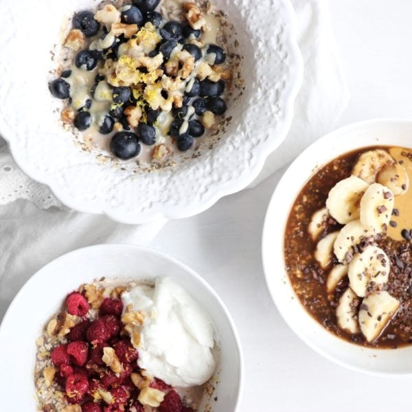 3 different versions of overnight oats placed in white round bowls. Ingredients include chia seeds and oats.