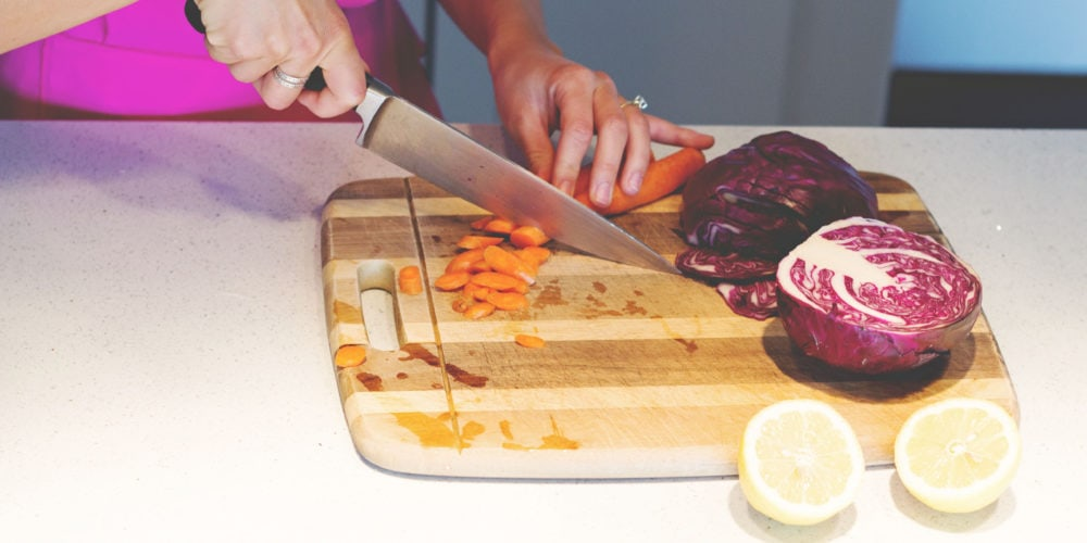 A photo of Registered Dietitian Lindsay Pleskot cutting carrots in the kitchen on a wooden cutting board.