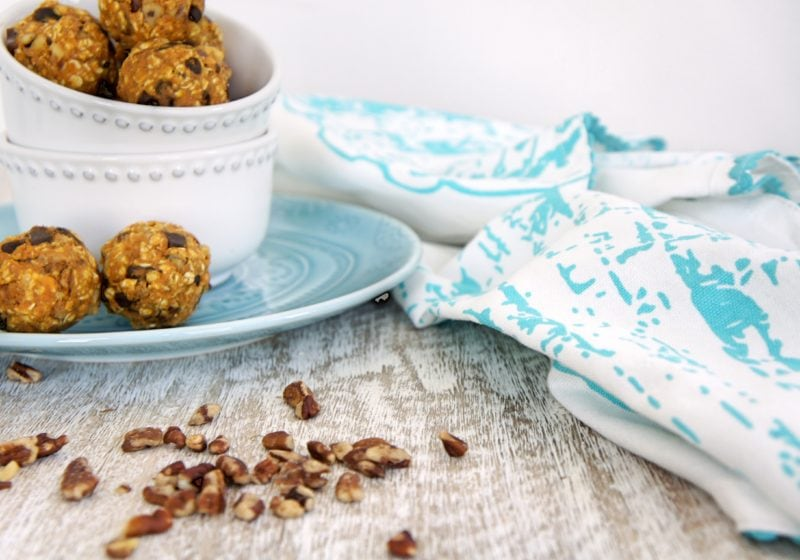 Pumpkin Pie Energy Bites placed in a stack of white round bowls on a blue plate. Ingredients include pumpkin puree, quick oats, dark chocolate chips, cinnamon, pecans, dates.