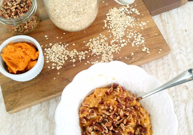 Pumpkin Pecan Oatmeal placed in a white round bowl. Ingredients include quick oats, water, pumpkin pie spice, pumpkin puree, walnuts, maple syrup, nut butter.