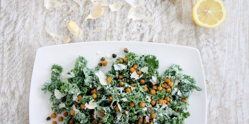 Lindsay's Famous Kale Caesar Salad placed on a white serving dish. Ingredients include kale, Greek yogurt, Parmesan, garlic, lemon, salt and pepper.