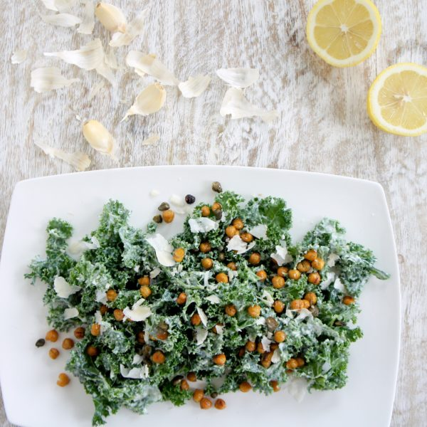 Lindsay's Famous Kale Caesar Salad placed on a white serving dish. Ingredients include kale, Greek yogurt, Parmesan, garlic, lemon, salt and pepper.