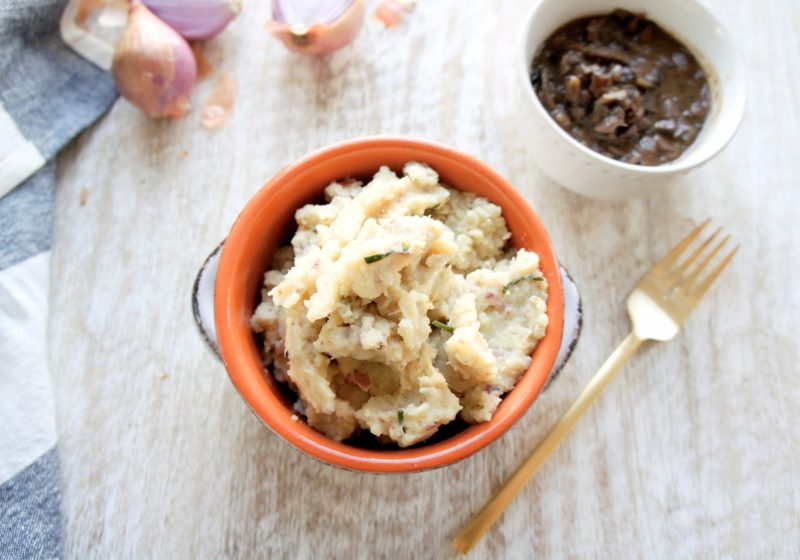Creamy Red Potato and Cauliflower Mash placed in a round cocotte. Ingredients include red potatoes, cauliflower, garlic, grass fed butter, chives.