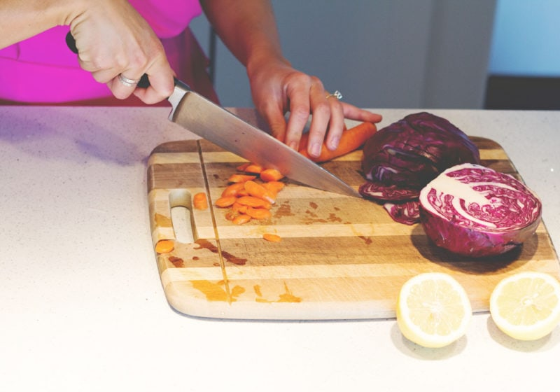 Registered Dietitian Lindsay Pleskot cutting carrots in the kitchen on a wooden cutting board.