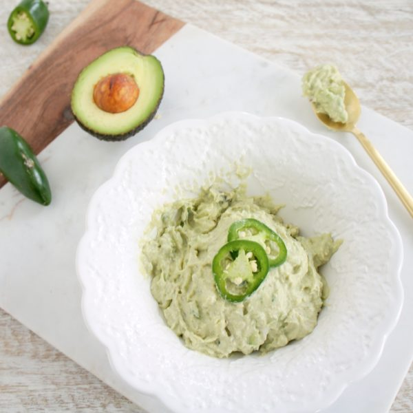 Fresh and Spicy Avopeno Dip in a white serving dish placed on a cutting board. Ingredients include Avocado, Greek yogurt, jalapeno, salt.