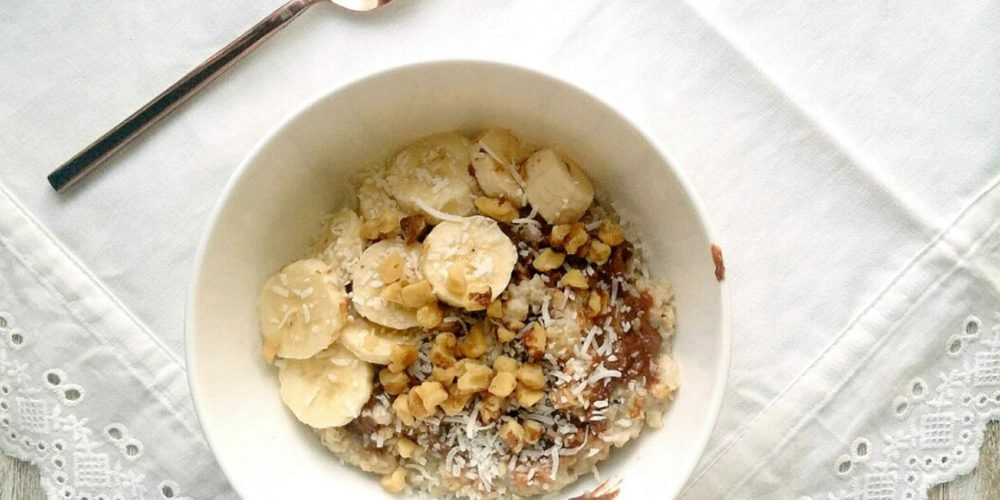 Chocolate Peanut Butter Oatmeal with Coconut, Walnuts, and Banana. Ingredients include quick oats, chocolate coconut peanut butter, shaved coconut, walnut pieces, banana slices.