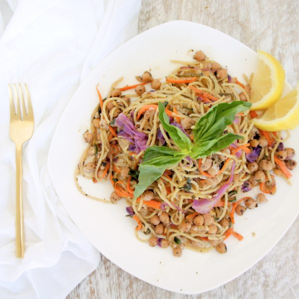 Lemon Pesto Rainbow Chickpea Pasta served in a white bowl with a gold fork and white kitchen towel placed beside it. Ingredients include spaghetti noodles, zucchini, purple cabbage, garlic, chickpeas.