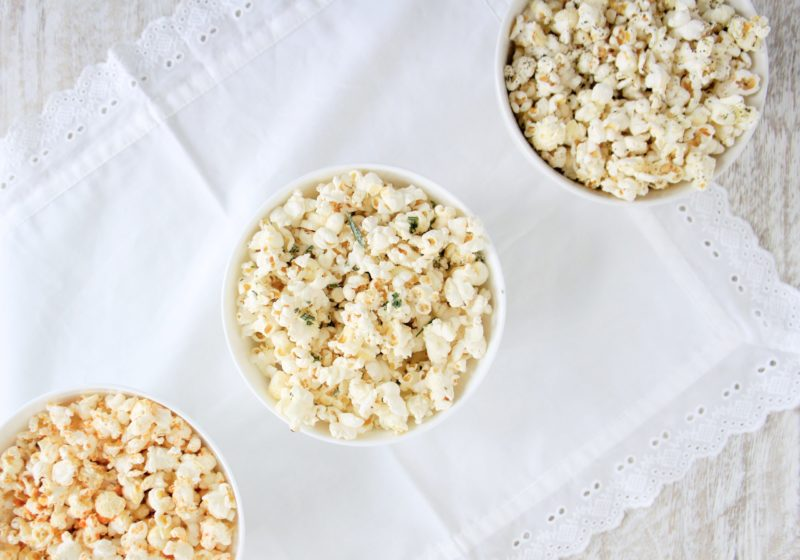 Popcorn three different ways served in white round bowls placed on a white table cloth.