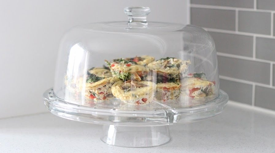 Muffin Tin Frittatas in a clear serving tray. Ingredients include eggs, milk, avocado oil, garlic, red onion, mushrooms, kale, red pepper, cherry tomatoes, cheddar cheese.