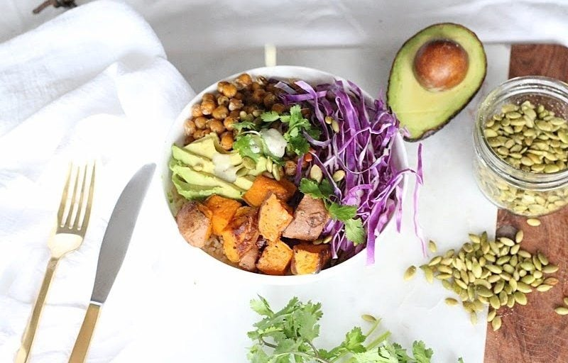 Buddha Bowl with Lemon Tahini Dressing served in a white round bowl. Ingredients include brown rice, yam, chickpeas, avocado oil, cabbage, carrots, avocado, pumpkin seeds, cilantro.