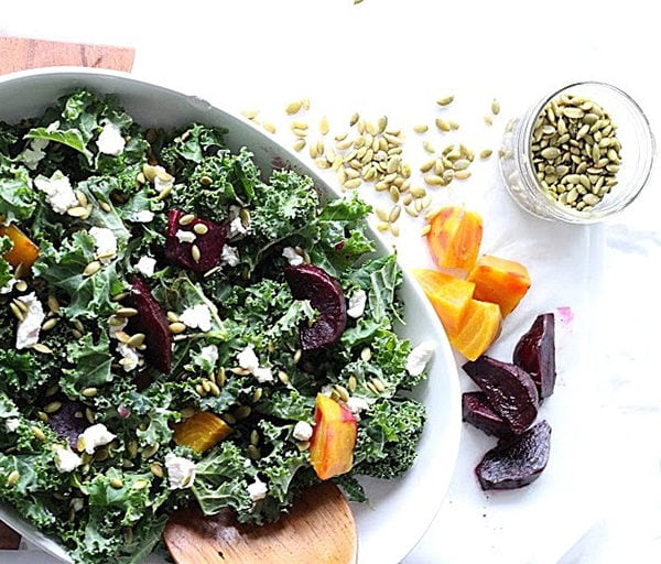 Roasted Beet and Kale Salad with Lemon Tahini Dressing served in a white round bowl. Ingredients include curly kale, golden beets, red beets, lentils, cheese, pumpkin seeds.
