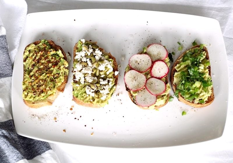 Four versions of avocado toast placed on a white serving plate. Ingredients include sprouted grain bread and avocado.