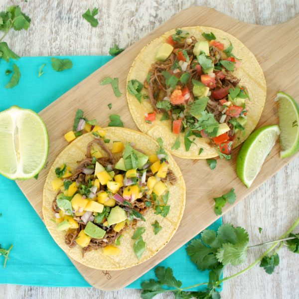 Slow Cooker Carne Asada Tacos served on a wooden cutting board with lime wedges. Ingredients include steak, chili, cumin, onion, garlic, cayenne.