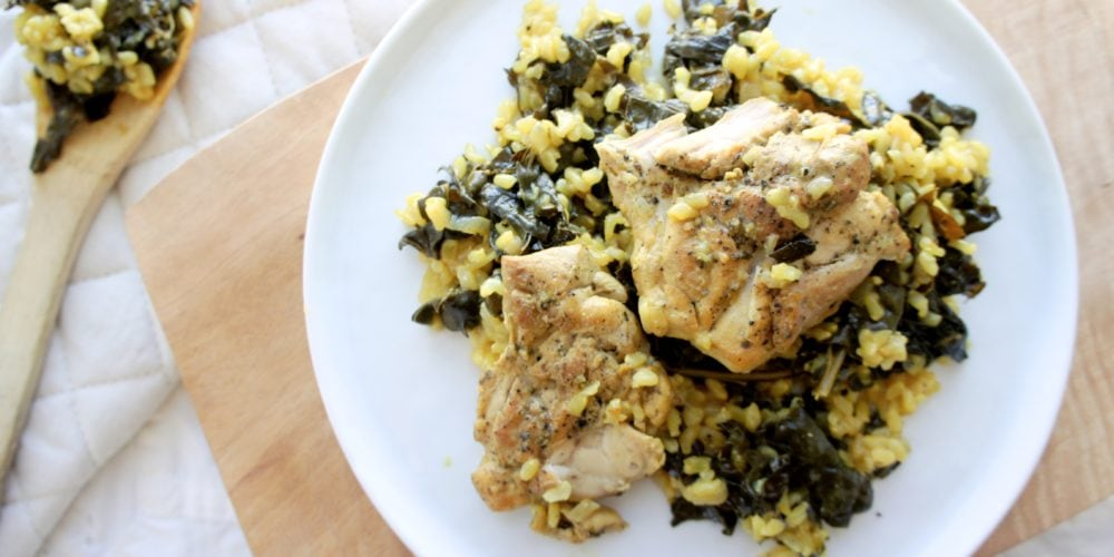 One Pan Turmeric Lemon Rice and Chicken with Kale served on a white round plate placed on a wooden cutting board. Ingredients include chicken thighs, pepper, olive oil, shallot, cumin, turmeric, curly kale, brown rice, lemon, chicken stock, Greek yogurt.