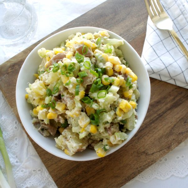 Light and Creamy Red Potato Salad placed in a white round bowl on a wooden cutting board with a napkin and golden fork beside the bowl. Ingredients include red nugget potato, corn, cheese, celery, onions.