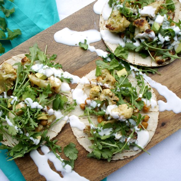 Three Crunchy Roasted Cauliflower Chickpea Tacos placed on a wooden cutting board on top of a blue kitchen towel.