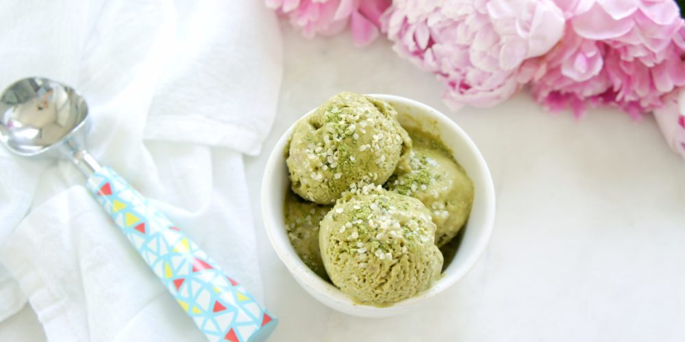 Matcha Banana Hemp Ice Cream scooped into a white round bowl placed on a white surface with an ice-cream scoop, white kitchen towel, and pink peonies beside it.