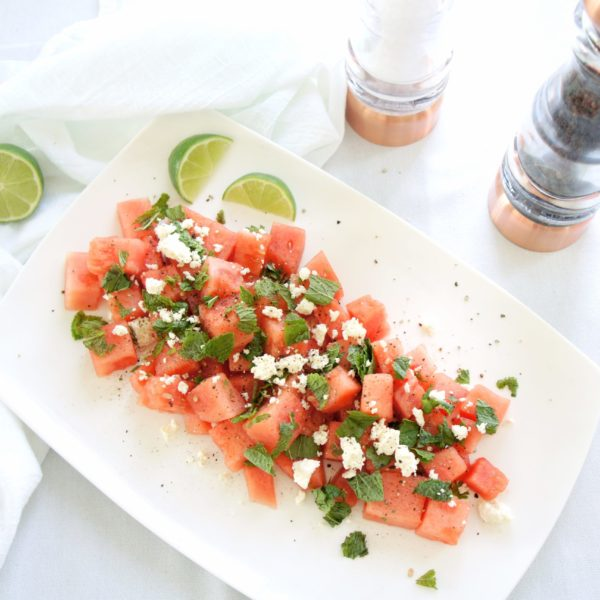 Fresh Watermelon, Mint, and Feta Salad placed on a white serving dish with lime wedges and a salt and pepper shaker placed beside it.