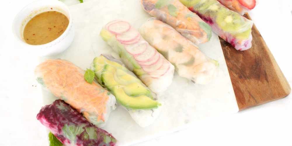 Summer Rolls placed on a cutting board with a serving of peanut sauce beside them. Ingredients include rice paper wrap, rice noodles, protein, vegetables, avocado, mint.
