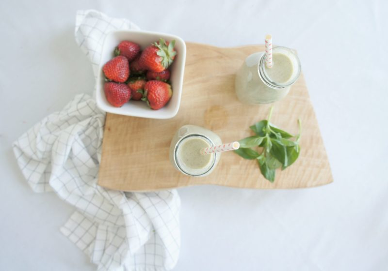 Two Strawberry Basil Smoothies in jars with straws placed on a wooden cutting board with a white bowl of strawberries and basil leaves.