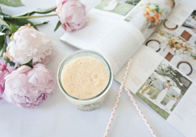 Bridal Smoothie in a glass jar placed beside two straws, a book, and purple peonies.