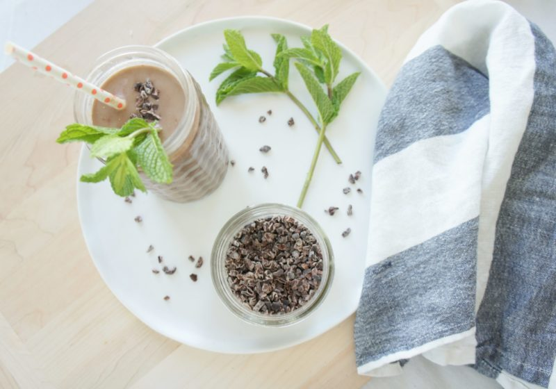 After 8 Chocolate Mint Protein Smoothie poured into a jar class placed on a white serving plate with a jar of chia seeds and a blue and white kitchen towel. Ingredients include almond milk, black beans, cacao nibs, banana, fresh mint, cocoa.