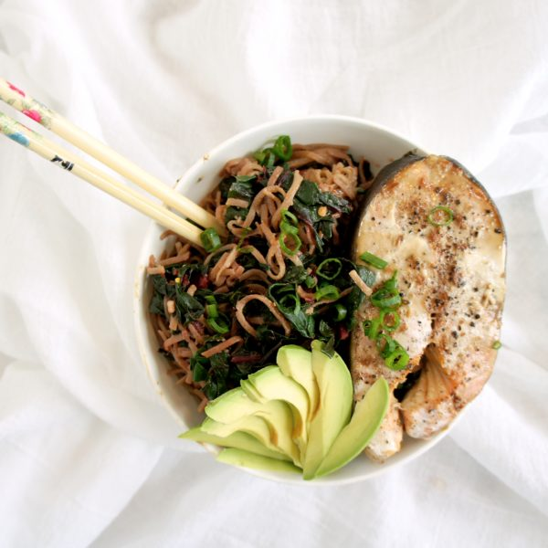 A noodle bowl with chopsticks on a white sheet. Ingredients include noodles, avocado.