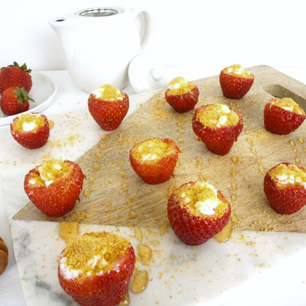 Strawberry Cheesecake Bites placed on a food photography board. Ingredients include strawberries, goat cheese, graham cracker crumbs.