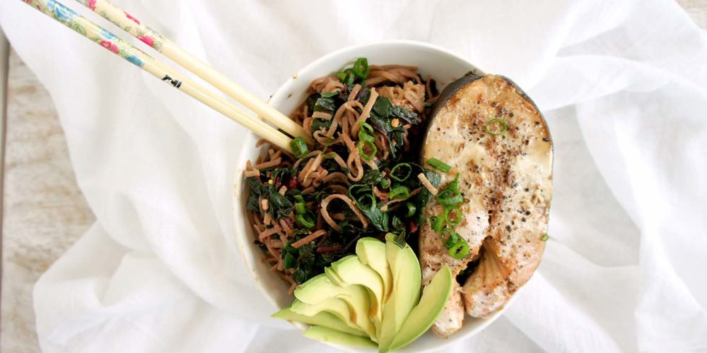 Salmon Soba Noodle Bowl placed in a white round bowl with chopsticks placed on a white sheet. Ingredients include salmon, avocado, soba noodles.