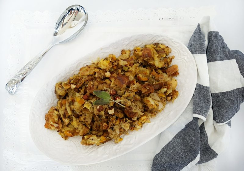 Sage and Apricot Sourdough Stuffing on a white serving plate with a striped kitchen towel placed beside and a silver serving spoon. Ingredients include sourdough bread, chicken stock, butter, onions, celery, hazelnuts, sage, apricots.