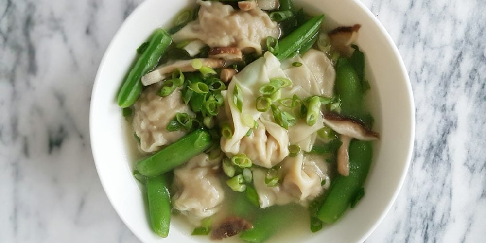 Famous Jang's Wonton Soup in a white round bowl on a marble surface. Ingredients include wontons, eggs, pork, turkey, chestnuts, ginger, chili, garlic, green onions, chicken stock, snow peas, mushroom, hot sauce.