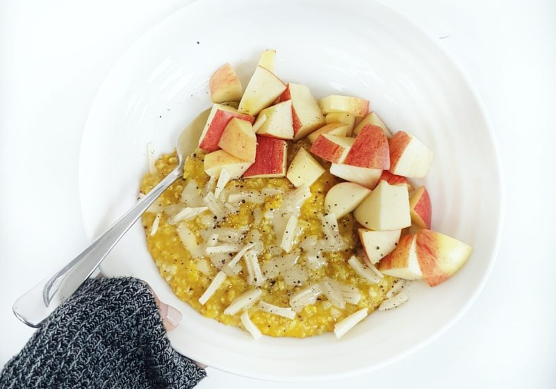 Registered Dietitian Lindsay Pleskot holding a white round bowl of Golden Oats with Apple and Cheddar. Ingredients include oats, water, apple.