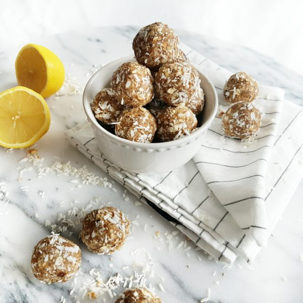 Lemon Coconut Bliss Balls placed in a white round bowl on striped kitchen towels with a sliced lemon placed beside it. Ingredients include lemon zest, pitted dates, almonds, unsweetened coconut, oats.