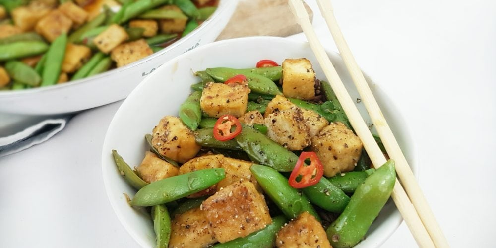 Crispy Black Pepper and Maple Tofu Snap Pea Stir Fry placed in a white round bowl with chopsticks. Ingredients include snap peas, tofu, soy sauce, garlic, ginger, chili, green onions.