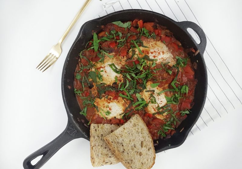 Shakshuka in a cast iron skillet placed on a white surface with a gold fork and striped kitchen towel. Ingredients include garlic, chili flakes, red pepper, diced tomatoes, tomato sauce, eggs, Parmesan, basil, multigrain sourdough.