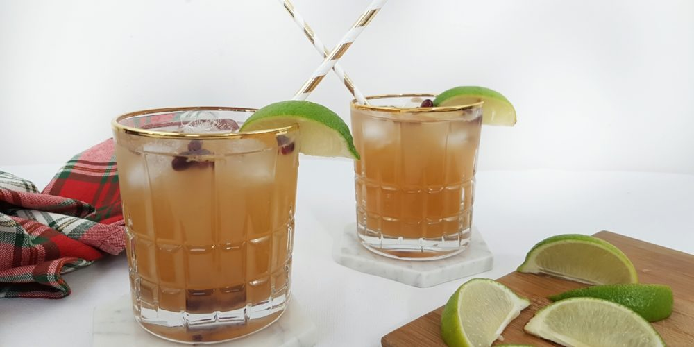 Ginger Pomegranate Kombucha Moscow Mule poured into two glasses with striped straws with a cutting board an lime wedges place beside. Ingredients include ice, vodka, ginger kombucha, pomegranate seeds, lime.