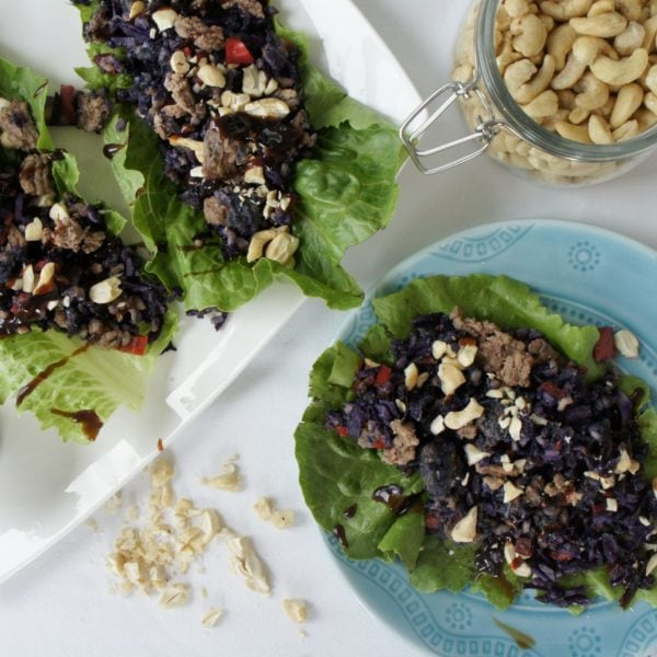 Shanghai Lettuce Wraps place on a white serving dish and a round blue plate. Ingredients include garlic, ginger, mushrooms, lettuce, red pepper, cabbage, brown rice, cashews, ground beef, soy sauce, hoisin sauce.