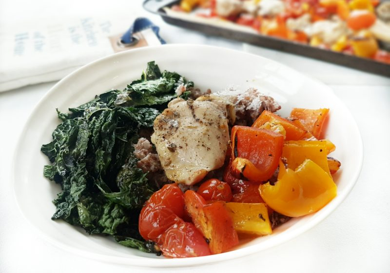 One Pan Greek Chicken with Blistered Tomatoes and Peppers in a white round bowl. Ingredients include bell pepper, cherry tomatoes, chicken thighs, Greek spice mix, lemon.
