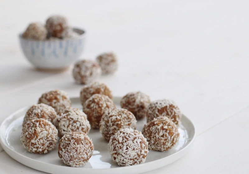salted caramel energy balls rolled in shredded coconut served on a white plate